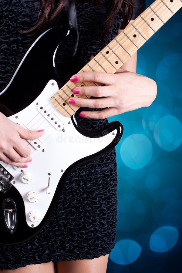 Frau, die auf Gitarre spielt stockfoto