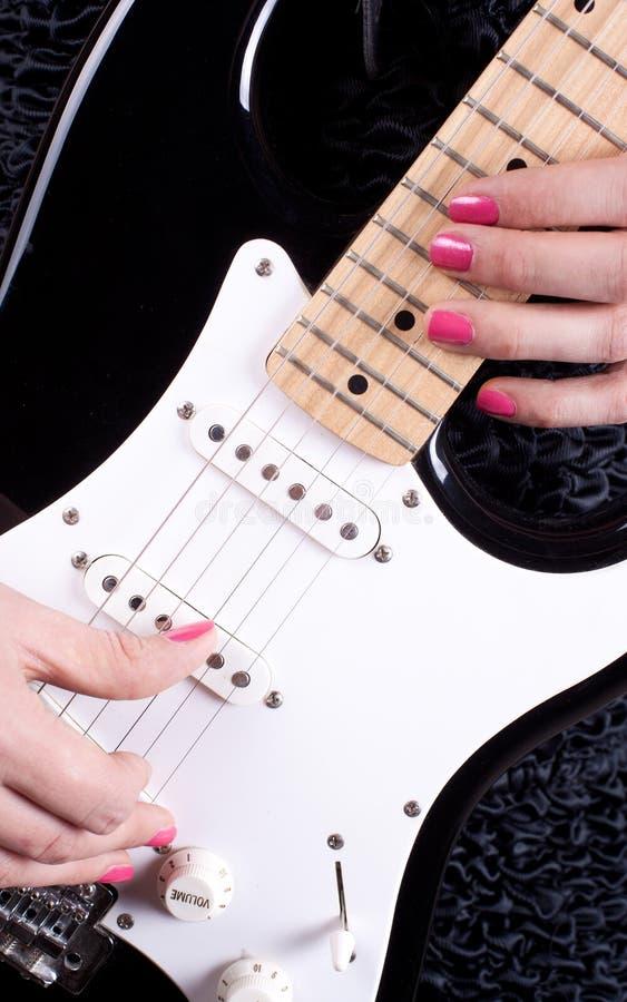 Frau, die auf Gitarre spielt lizenzfreies stockfoto