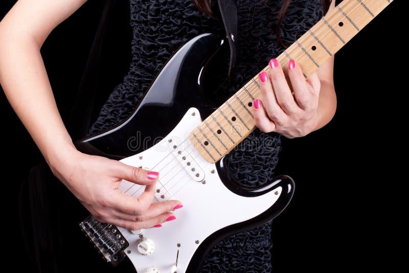 Frau, die auf Gitarre spielt stockfotografie