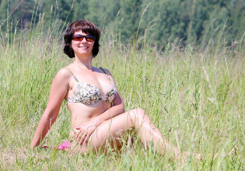Frau, die auf Gras ein Sonnenbad nimmt lizenzfreie stockfotos