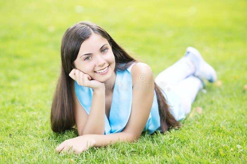 Frau, die auf Gras legt stockbilder