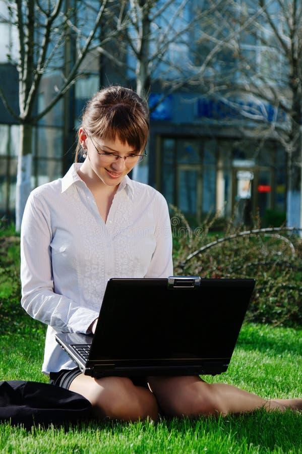 Frau, die auf Gras mit Laptop liegt lizenzfreie stockbilder