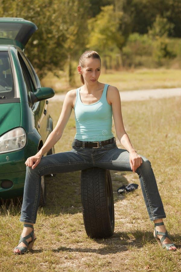 Frau, die auf Gummireifen sitzt stockfoto