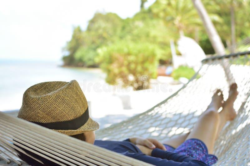 Frau, die auf Hängematte mit Hut sich entspannt stockbild