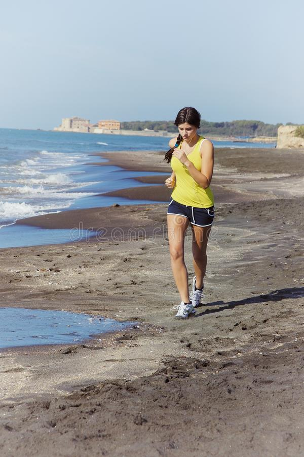 Frau, die auf hörender Musik des Strandes rüttelt stockfotos