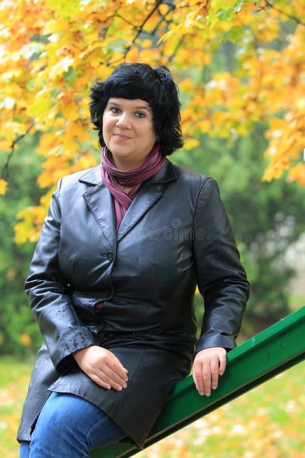 Frau, die auf Handlauf sitzt lizenzfreies stockfoto