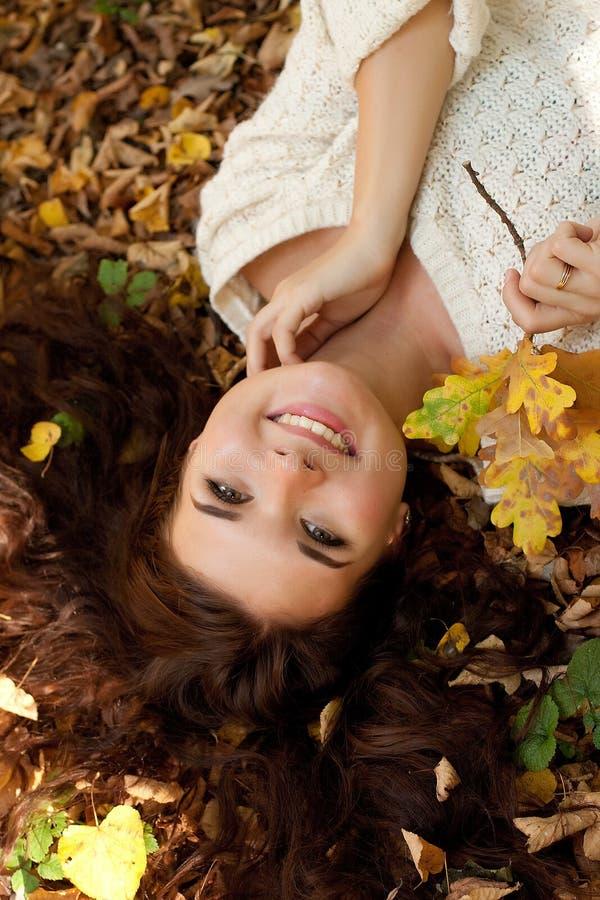 Frau, die auf Herbstlaub, Porträt im Freien liegt lizenzfreies stockfoto