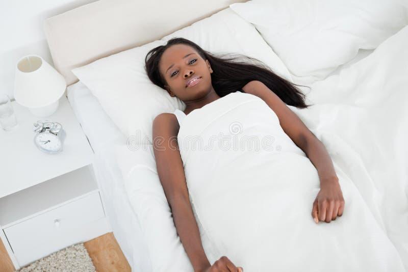 Frau, die auf ihrem Bett liegt stockfotos