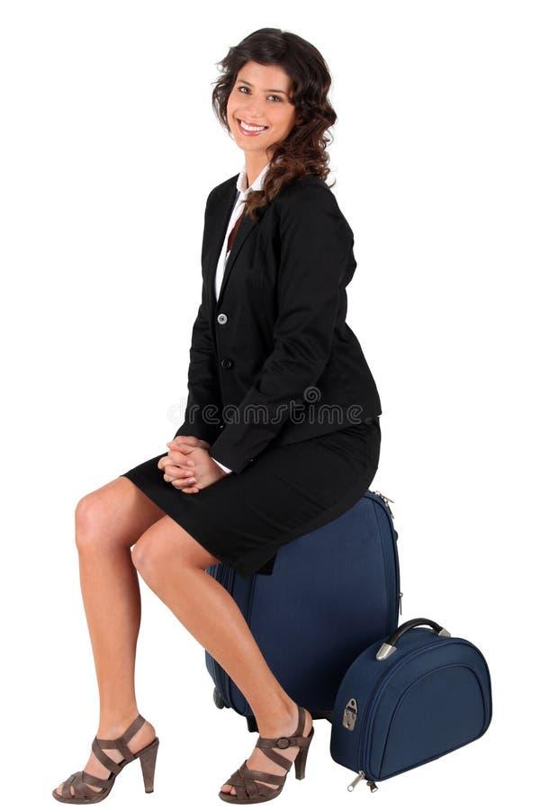 Frau, Die Auf Ihrem Koffer Sitzt Lizenzfreies Stockbild