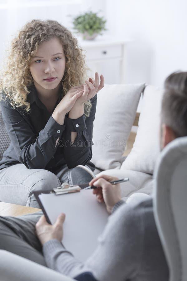 Frau, die auf ihren Psychotherapeuten hört stockfotografie