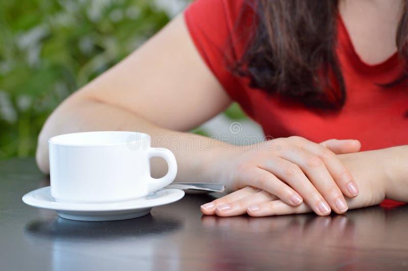 Frau, die auf jemand an einer Kaffeestube mit einem Tasse Kaffee vor ihm wartet lizenzfreie stockfotos