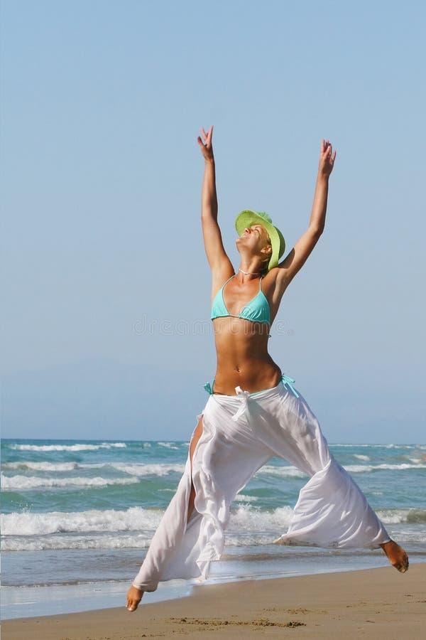 Frau, die auf Küstenlinie am Strand steht stockfotografie