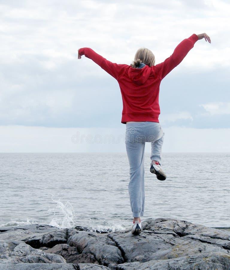 Frau, die auf Klippe trainiert lizenzfreie stockfotos