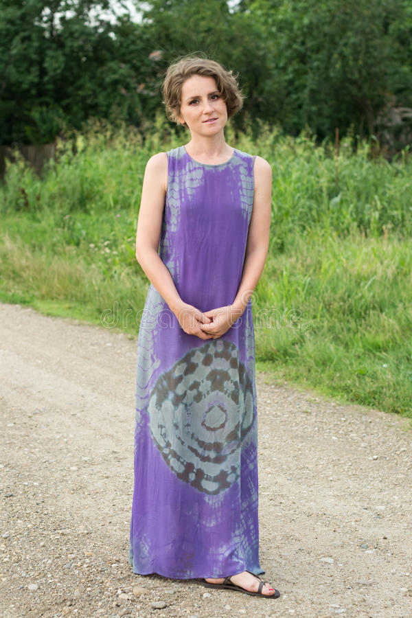 Frau, die auf ländlicher Straße steht lizenzfreie stockbilder