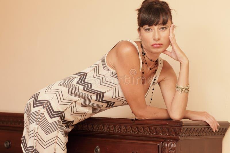 Frau, die auf Möbeln sich lehnt stockfoto