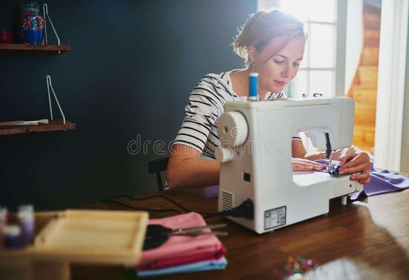 Frau, die auf Nähmaschine näht stockfoto