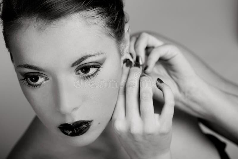 Frau, die auf Ohrring sich setzt lizenzfreie stockfotos
