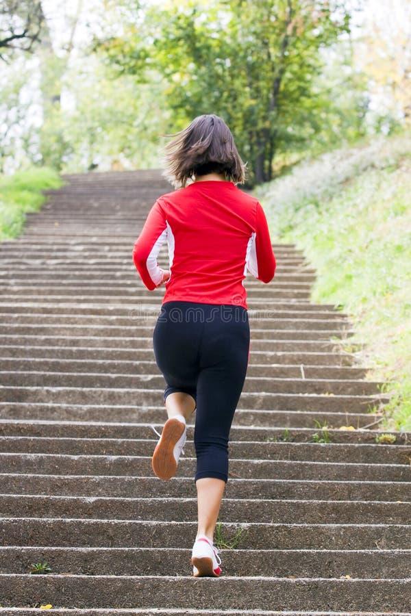 Frau, die auf Parktreppen läuft stockfoto