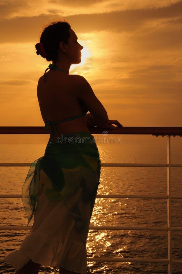 Frau, die auf Plattform des Kreuzschiffs steht stockfoto