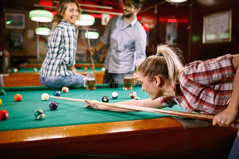 Frau, die auf Poolball beim Spielen von Billard zielt lizenzfreies stockfoto