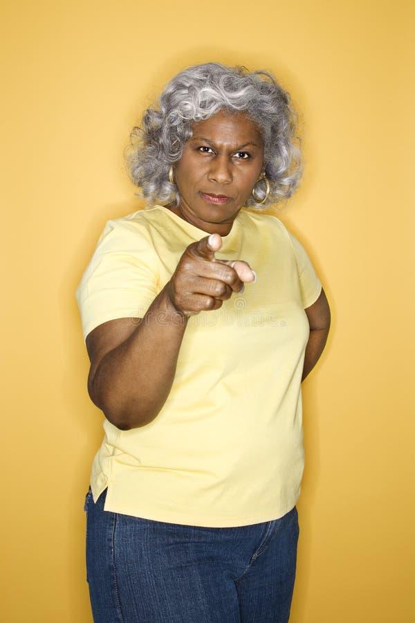 Frau, die auf Projektor zeigt. lizenzfreie stockfotos