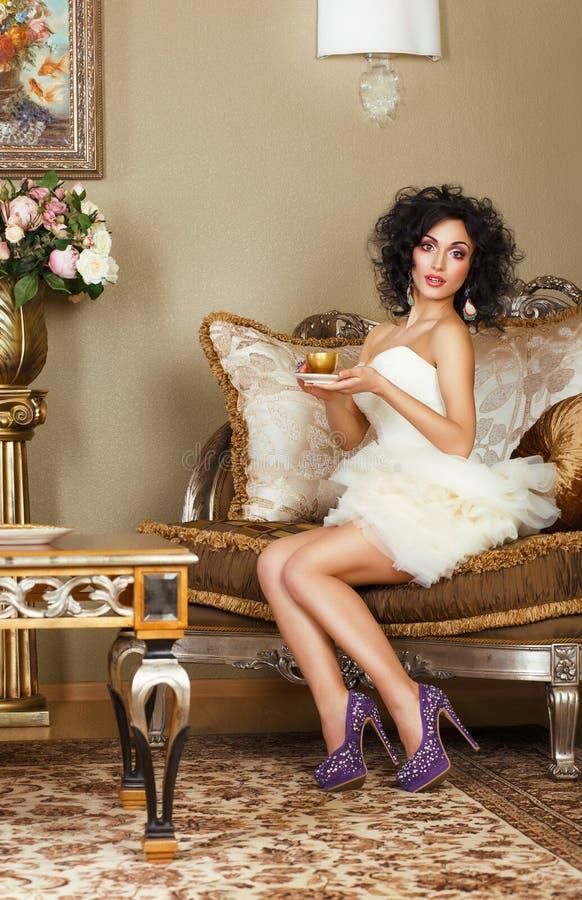 Frau, die auf Retro- Couch mit Kappe des Kaffees sitzt. Klassischer Innenraum lizenzfreies stockfoto