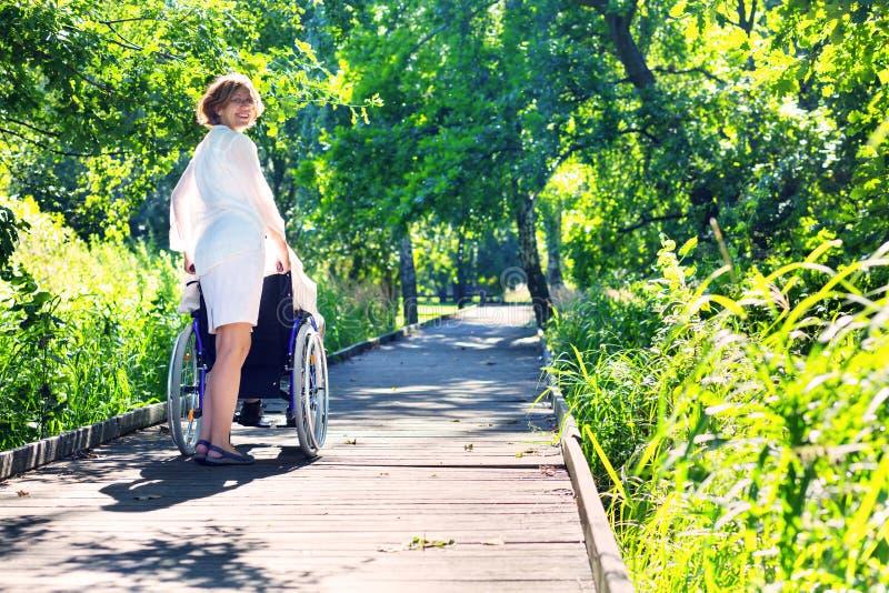 Frau, die auf Rollstuhl im Park drückt stockbild
