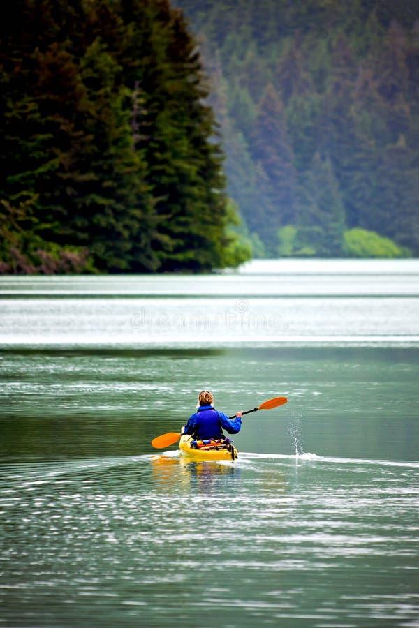 Frau, die auf ruhigem See Kayak fährt lizenzfreie stockbilder