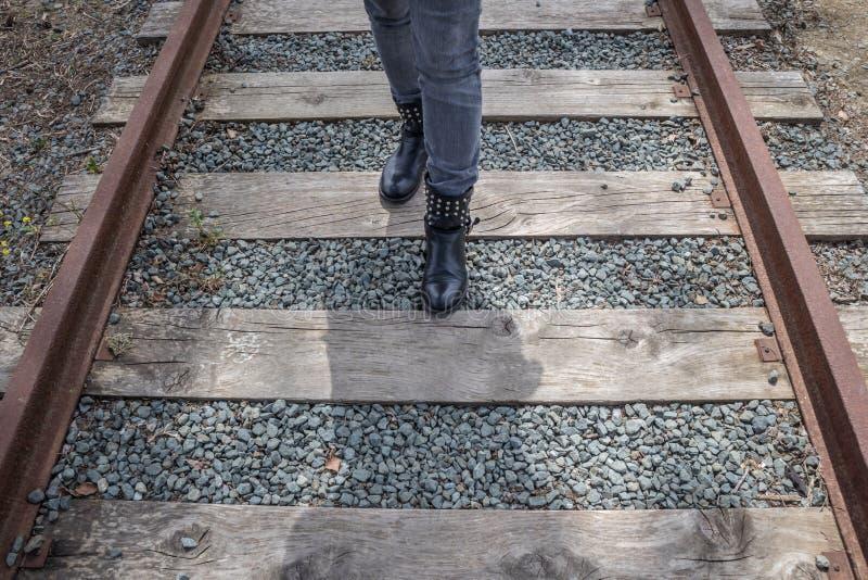 Frau, die auf Schienen geht stockbild