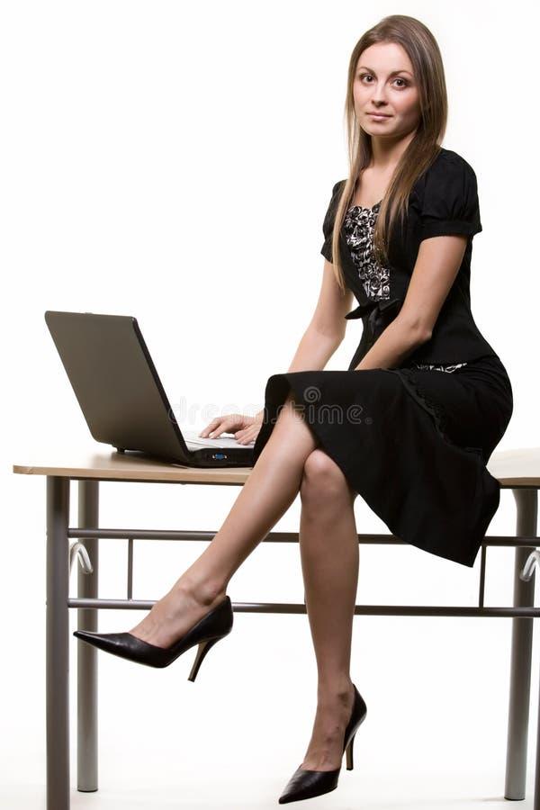 Frau, die auf Schreibtisch sitzt lizenzfreie stockfotografie