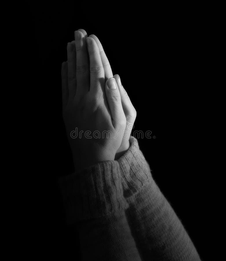 Frau, die auf schwarzem Hintergrund betet stockbild
