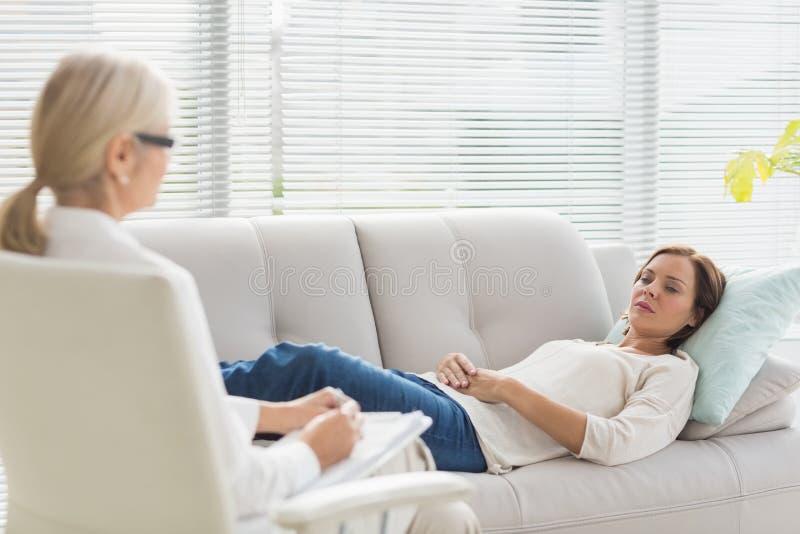 Frau, die auf Sofa bei der Unterhaltung mit Therapeuten liegt lizenzfreie stockfotografie