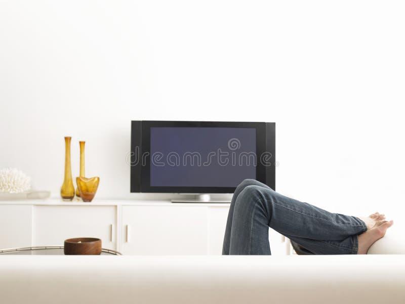 Frau, die auf Sofa liegt lizenzfreie stockfotos