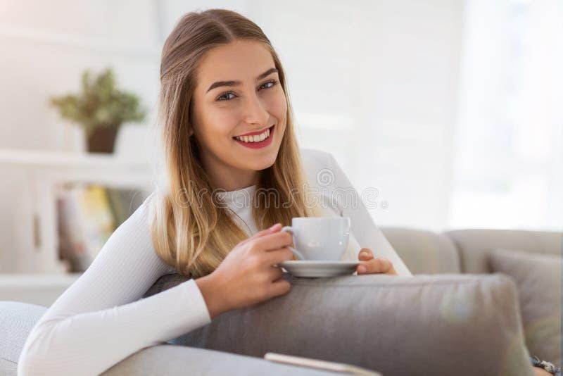 Frau, die auf Sofa mit Tasse Kaffee sitzt lizenzfreies stockfoto