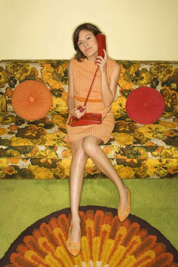 Frau, die auf Sofa sitzt. lizenzfreie stockfotografie