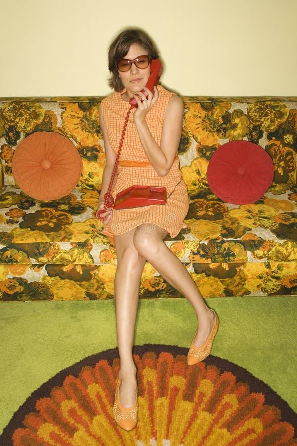 Frau, die auf Sofa sitzt. lizenzfreies stockfoto