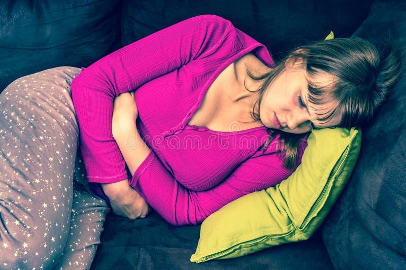 Frau, die auf Sofa und Händchenhalten auf ihrem Magen liegt stockfotos
