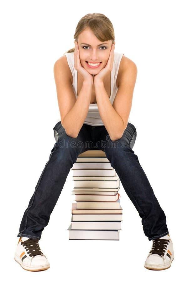 Frau, die auf Stapel Büchern sitzt lizenzfreie stockfotografie