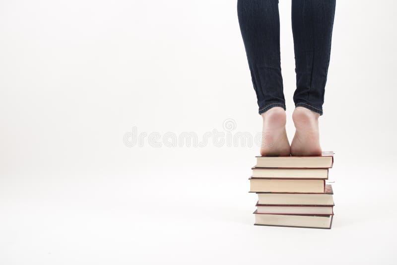 Frau, die auf Stapel von Büchern steht stockfotos
