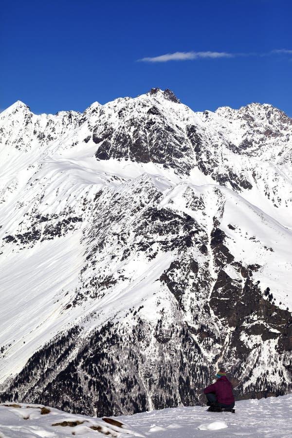 Frau, die auf Steigung im Winterschneeberg am Sonnentag stillsteht stockfotografie