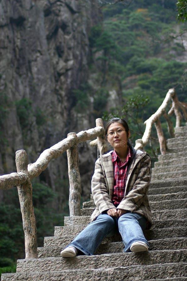 Frau, die auf steilen Jobstepps sitzt stockbild