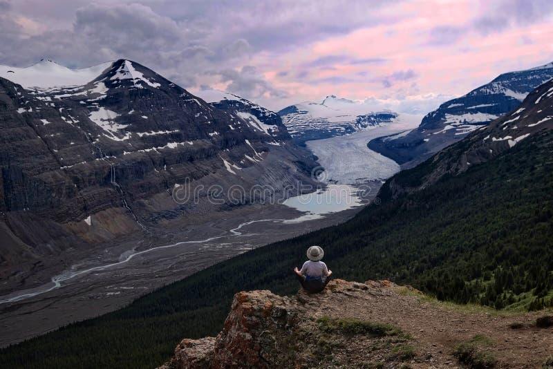 Frau, die auf steiler Klippe über Gletscher Kolumbiens Icefield und einem Morainesee meditiert lizenzfreie stockfotos