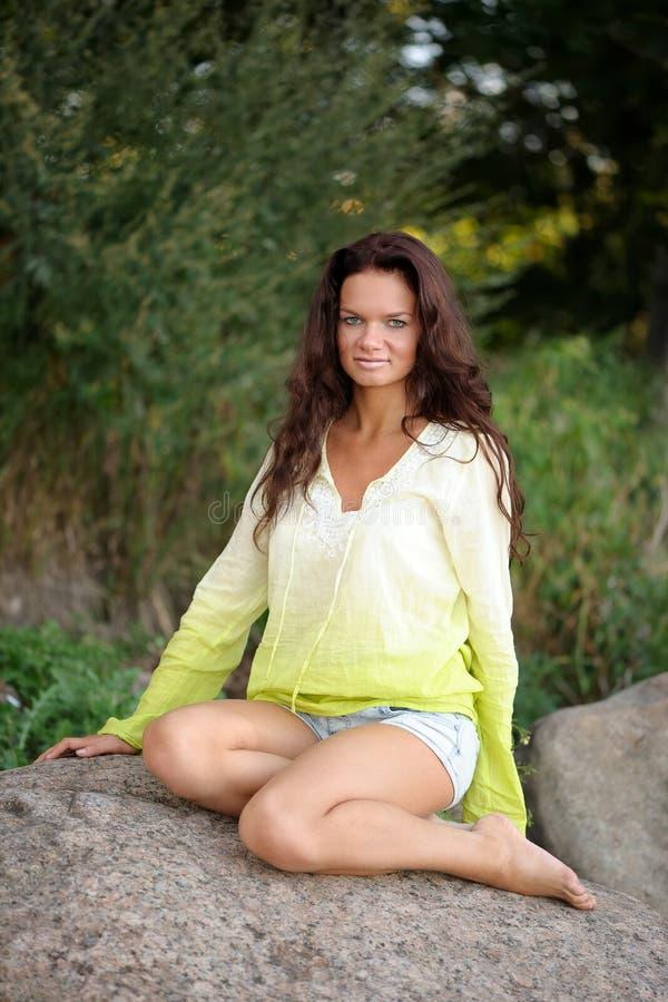 Frau, die auf Steinen sitzt lizenzfreie stockfotos