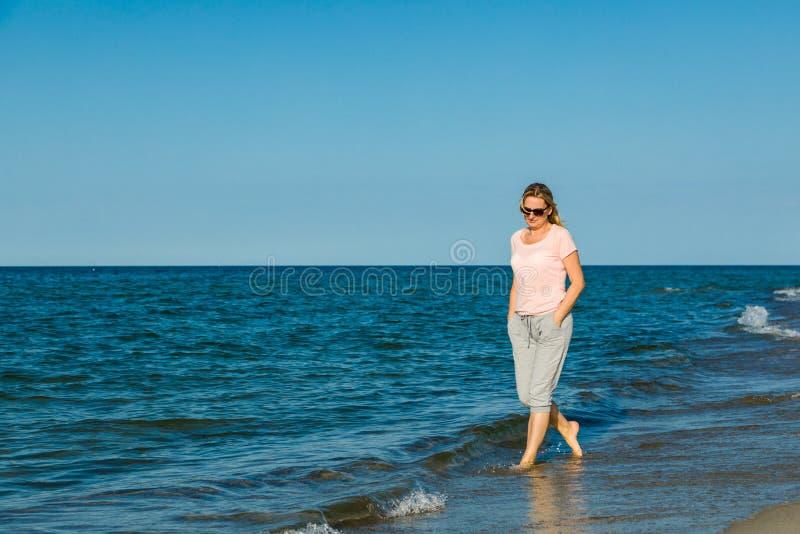 Frau, die auf Strand aufweckt stockfotografie