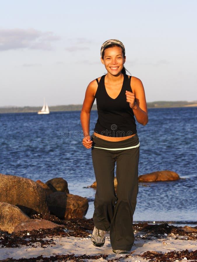 Frau, die auf Strand läuft stockfoto