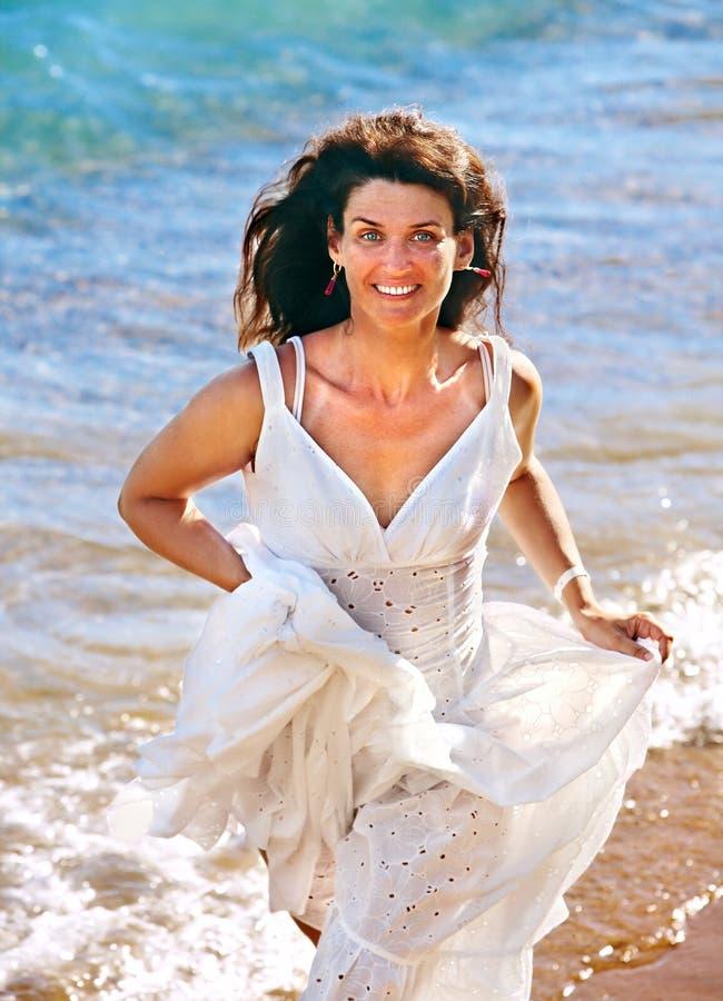 Frau, die auf Strand läuft stockfotografie