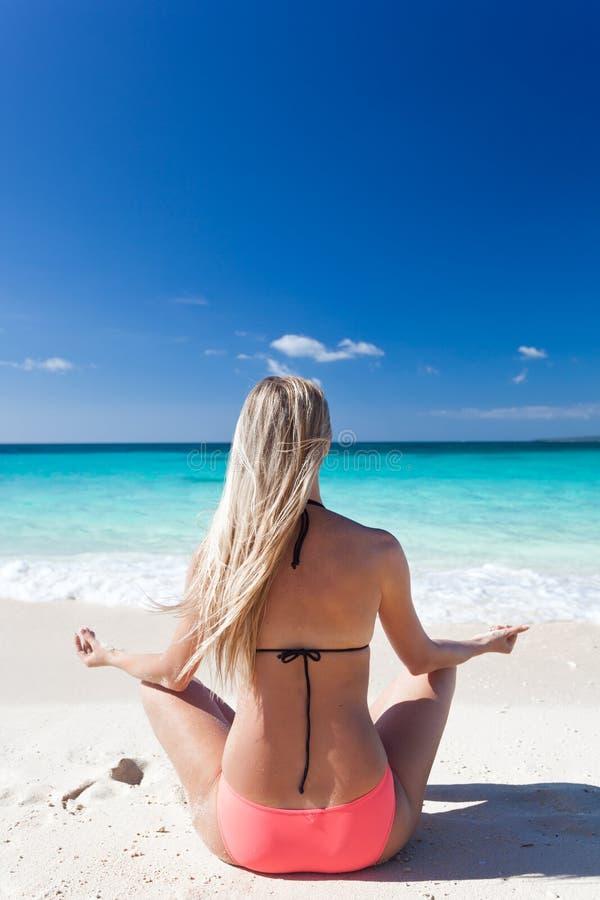 Frau, die auf Strand in Lotussitz meditiert lizenzfreie stockfotografie