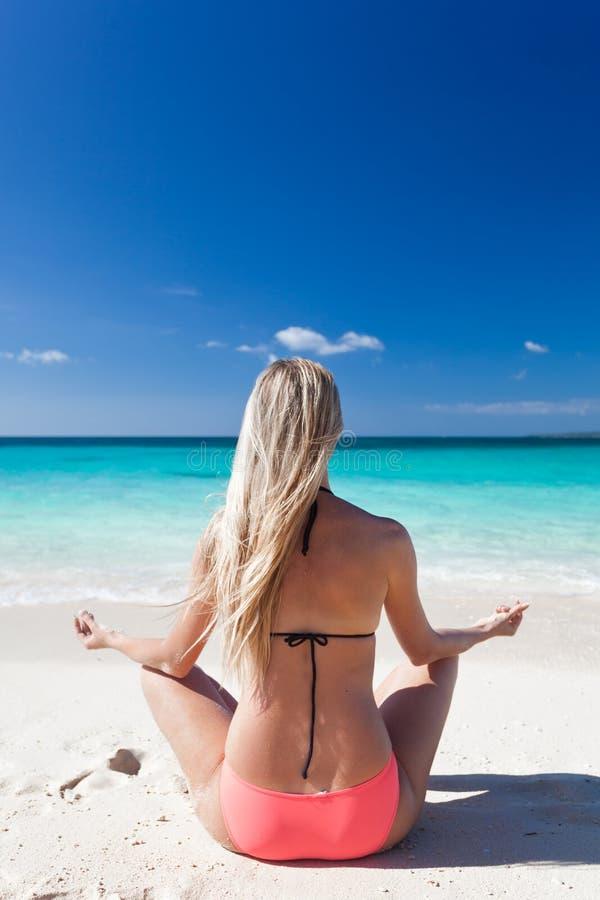 Frau, die auf Strand in Lotussitz meditiert stockbilder