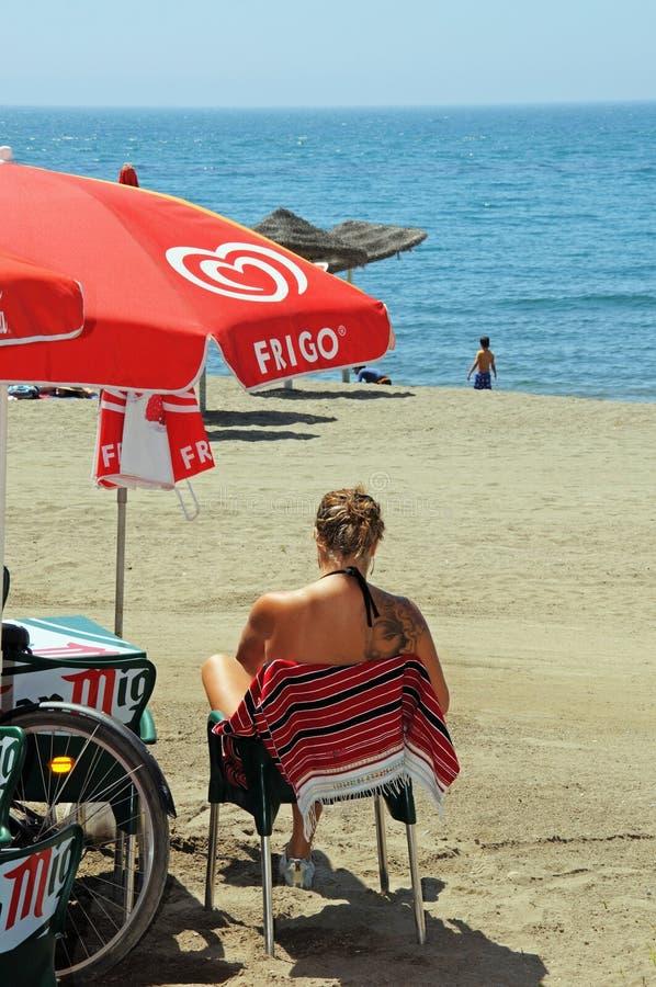 Frau, die auf Strand, Màlaga, Spanien sitzt lizenzfreies stockbild