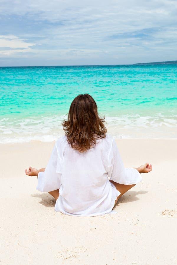 Frau, die auf Strand meditiert stockbild